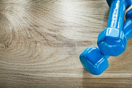 Pair of blue dumbbell weights on wooden board sports training co