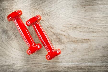 Set of red dumbbells on wood board top view fitness concept