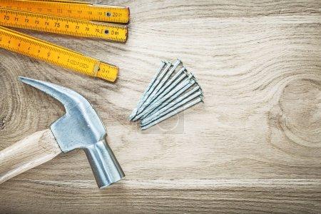 Photo pour Bouchent la vue de marteau mètre en bois construction clous sur planche de bois de construction concept. - image libre de droit