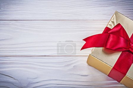 Birthday gift box with red satin tape on wooden board holidays c