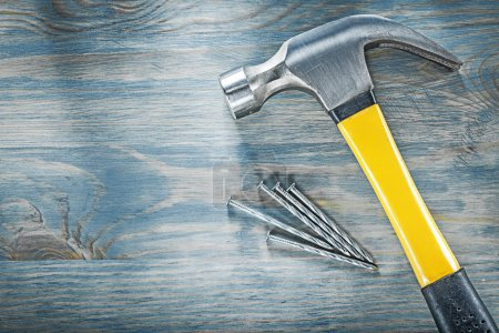 Photo for Composition of claw hammer stainless nails on wooden board construction concept. - Royalty Free Image