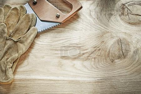 Pair of protective gloves sharp handsaw on wooden board construc