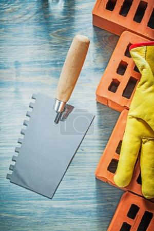 Palette knife red bricks safety gloves on wood board bricklaying