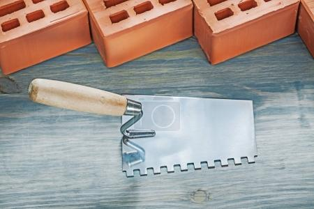 Red bricks construction spatula on wood board bricklaying concep
