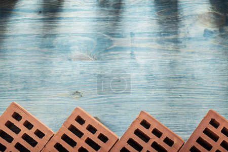 Red bricks on wooden board horizontal version building concept