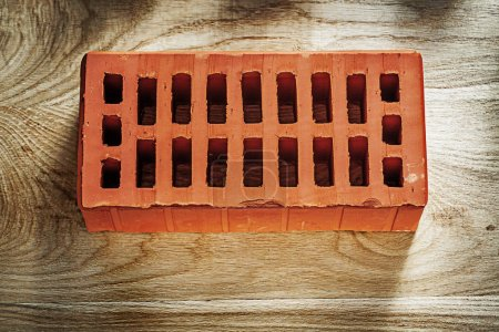 Red construction brick on wooden board bricklaying concept