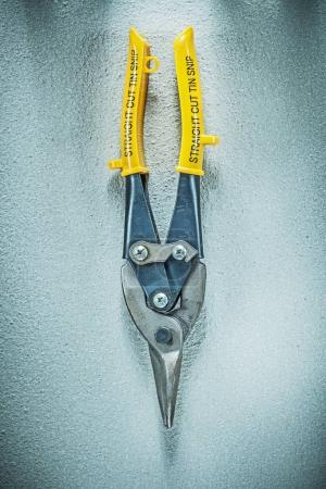 Straight cut tin snips on concrete surface construction concept