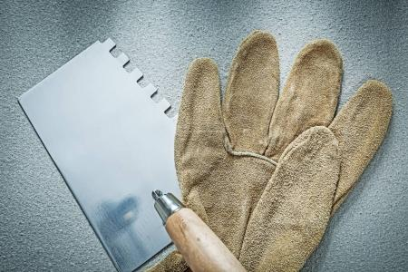 Bricklaying trowel working gloves on concrete background constru
