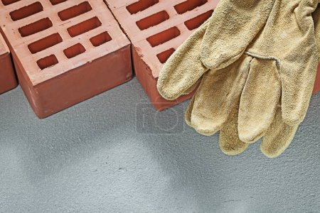 Orange bricks leather working gloves on concrete surface buildin