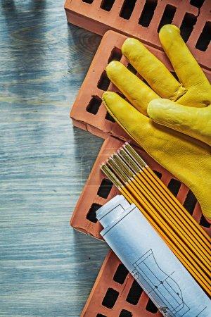 Blueprints protective gloves red bricks wooden meter on wood boa