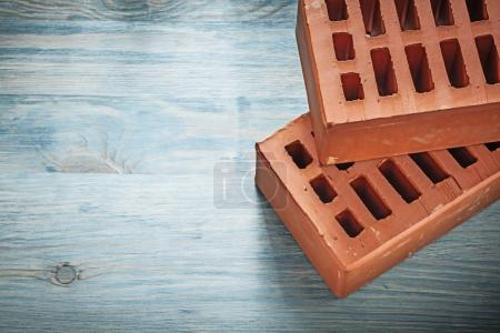 Pair of red bricks on wood board construction concept