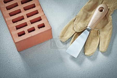 Red bricks protective gloves plastering trowel on concrete backg