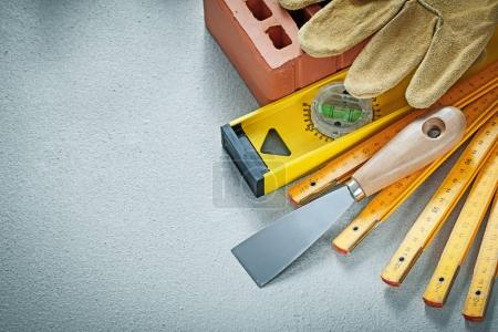 Photo for Red brick working gloves plastering trowel construction level wooden meter on concrete background bricklaying concept. - Royalty Free Image