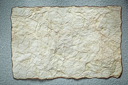 Vintage crumpled paper sheet on grey background top view