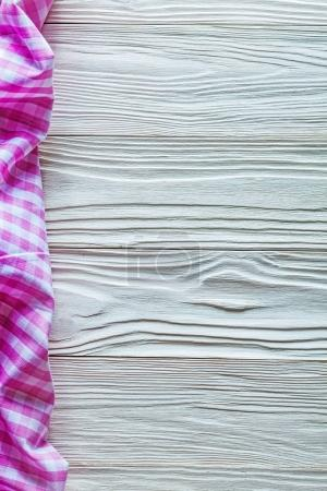 Pink cotton tablecloth on wooden board