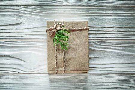 Handmade present box with green thuya branch top view celebratio