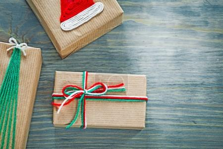 Assortment of handmade Christmas gift boxes on wooden board holi