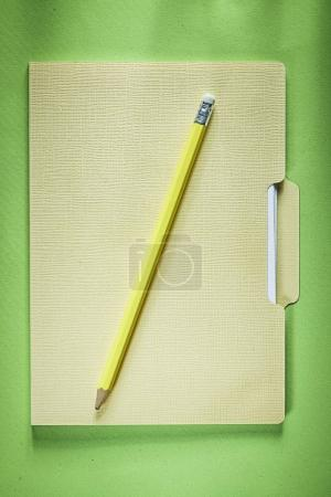 Cardboard office folder pencil on green background
