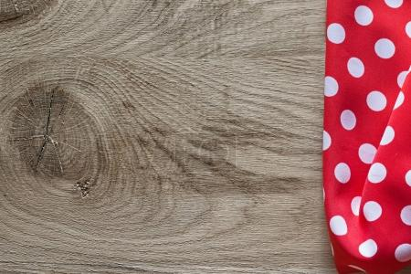 Red white cotton folded polka-dot tablecloth on wooden board hor