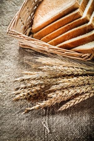 Wicker basket sliced bread rye ears on burlap background