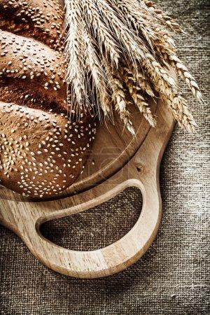 Chopping board bread rye ears on sacking background