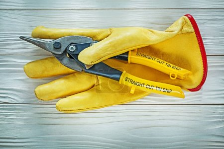 Protective gloves tin snip on wooden board
