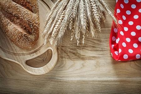 Bread carving board wheat ears red tablecloth on wooden backgrou