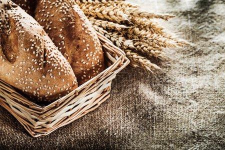 Wicker basket bread wheat ears on burlap background