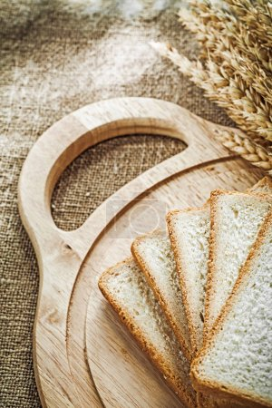 Carving board sliced bread wheat ears on sacking background