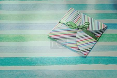 Present on blue striped fabric top view holidays concept