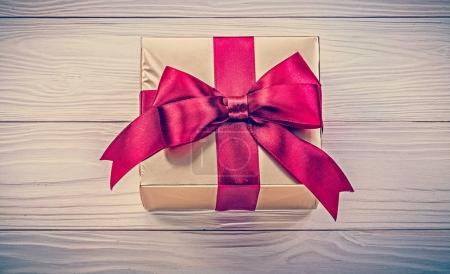 Wrapped present box on wooden board directly above holidays conc
