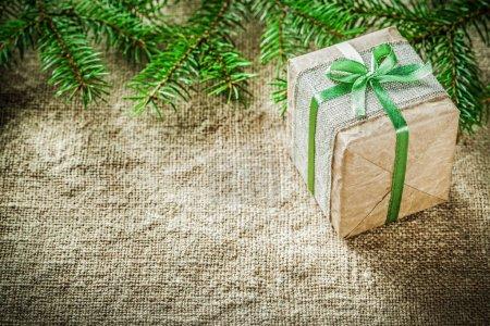 Pine tree branch handmade gift box on sacking background