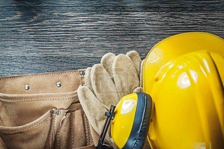 Photo pour Casque de construction cache-oreilles gants de protection ceinture d'outils sur panneau de bois . - image libre de droit