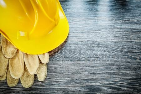Protective gloves hard hat on wooden board