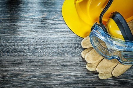 Safety gloves glasses earmuffs hard hat on wooden board