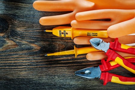 Photo for Dielectric gloves electric tester insulated cutting nippers pliers on wooden board. - Royalty Free Image