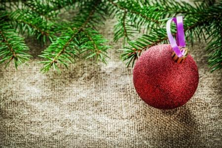 Pine tree branch Christmas bauble on sacking background