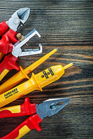Photo for Electric tester insulation strippers cutting nippers pliers on wooden board. - Royalty Free Image