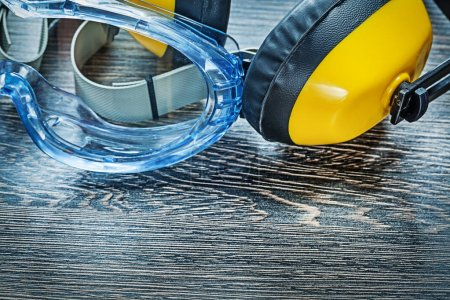 Safety glasses earmuffs on wooden board