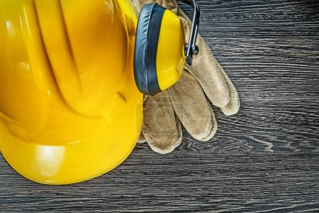 Hard hat earmuffs leather safety gloves on wooden board
