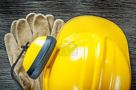 Building helmet earmuffs protective gloves on wood board