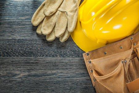 Photo pour Ceinture à outils en cuir gants de sécurité casque de construction sur panneau noir . - image libre de droit