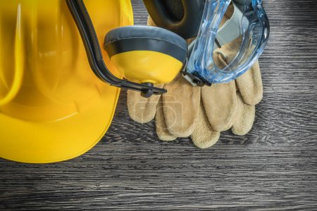 Protective leather gloves goggles earmuffs hard hat on wood boar