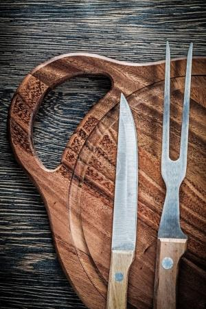 Meat fork knife wooden carving board on wood background