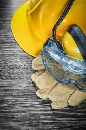Safety gloves glasses earmuffs building helmet on wooden board