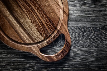 Round chopping board on wood background