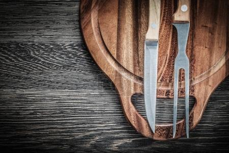 Composition of meat fork knife chopping board on vintage wooden