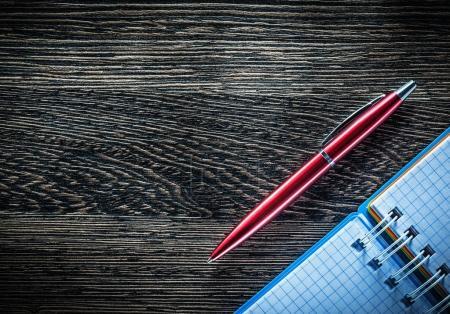 Biro pen spiral checked notebook on vintage wooden board