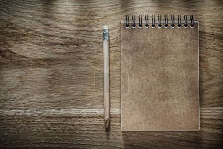 Pencil brown notebook on wooden board
