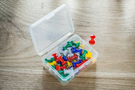 Set of push pins in plastic box on wooden board